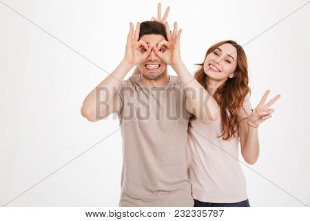 Amusing two people boyfriend and girlfriend fooling around while gesturing and making faces on camera isolated over white background