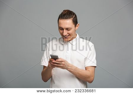 Image of cheerful young man standing isolated over grey wall. Looking aside using mobile phone.