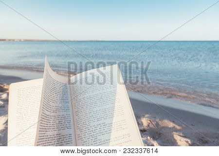 Relax concept. Open book on sand near the sea. Summer vacations still life. The text is transformed and not recognizable.
