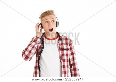 Attractive guy in casual t-shirt 17y wearing braces listening to favorite tune via wireless headphones and looking aside on copyspace isolated over white background