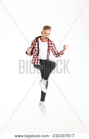 Full length image of ecstatic teen man wearing plaid shirt shouting and clenching fists on camera like winner or smart pupil isolated over white background