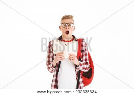 Portrait of a shocked schoolboy in eyeglasses with backpack reading a book and looking at camera isolated over white background