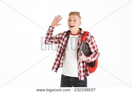 Portrait of a cheerful schoolboy in eyeglasses with backpack holding laptop computer and waving with hand isolated over white background