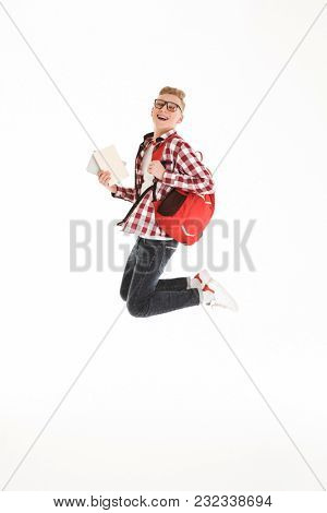 Full length portrait of a happy schoolboy in eyeglasses with backpack holding books and jumping isolated over white background