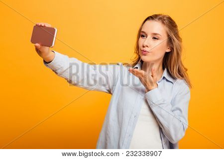 Portrait of a pretty young girl with braces taking a selfie with mobile phone isolated over yellow background