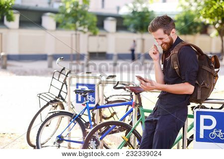 A Handsome Bearded Male In Casual Clothing Using A Phone Near Bicycle Parking.