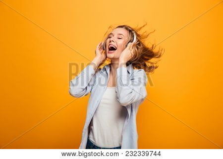 Photo of satisfied smiling woman 20s wearing braces in basic clothing expressing delight while listening to music on wireless earphones isolated over yellow background