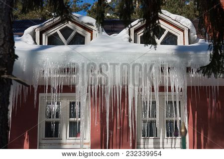 Ice Stalactite Hanging From The Roof At Spring Sunny Day
