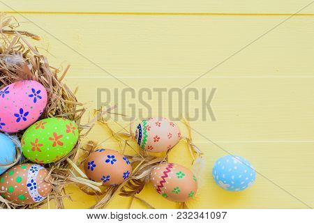 Happy Easter! Colorful Of Easter Eggs In Nest On Pastel Color Bright Yellow And White Wooden Backgro