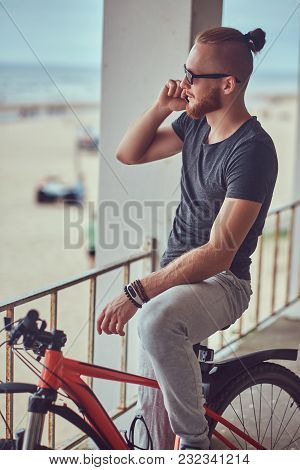 Handsome Redhead Male With A Stylish Haircut And Beard Dressed In Sportswear With A Bicycle, Talking