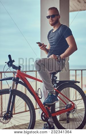 Handsome Redhead Male With A Stylish Haircut And Beard Dressed In Sportswear With A Bicycle, Using T