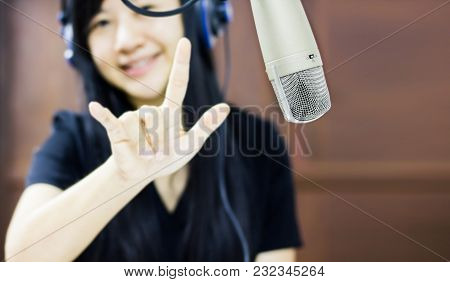 Microphone In Studio With Blurred Asian Women Smiling With Finger Symbol Of Love