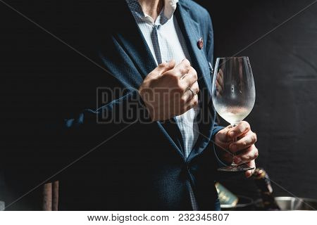Man Holds Glass Of Red Wine. A Lot Of Different Wine Glasses On The Table At Wine Tasting. People Co