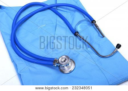 Medical Stethoscope Head Lying On Blue Doctor Uniform Closeup. Medical Tools And Instruments Shop, T