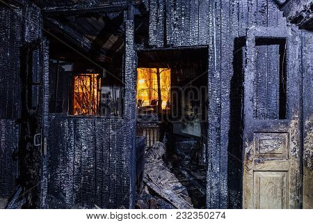 Burnt House. Burned Furniture, Door, Charred Walls And Ceiling.