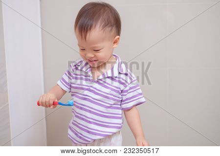 Cute Smiling Little Asian 18 Months / 1 Year Old Toddler Boy Child Wearing Purple Shirt Holding Toot