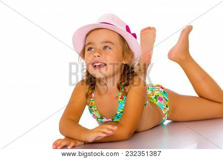 A Happy Little Girl In A Bathing Suit Lies And Sunbathes. The Concept Of A Family Vacation At Sea, S