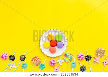 Sweets For Party Background. Macarons And Lollipop On Yellow Background Top View.