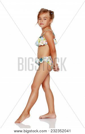 Tanned Little Girl In A Swimsuit. The Concept Of Summer Family Vacations In The Sea. Happy Childhood