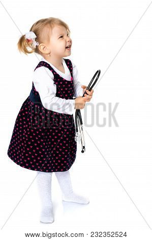 Little Girl Is Playing Doctor. She Has A Phonendoscope In Her Hands. Concept Happy Childhood, Game.