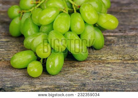 Ripe Bunch Of Green Grape On The Old Wooden Background