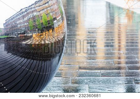 metal ball on the city square in a rainy day