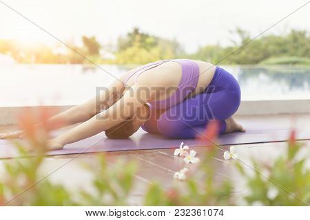 Portrait Of Woman Playing Yoga Beside Swimming Pool