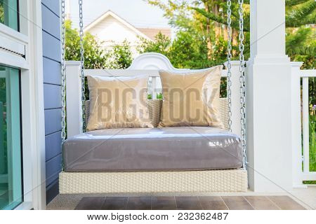 Brown Pillows On Modern Resin Hanging Swing With Chain In A Porch With Garden Background.