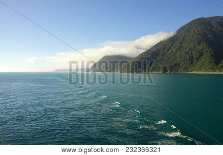 Wash From A Boat Spreading Across The Ocean. Forest Covered Hills Run Down To The Shoreline. The Sky
