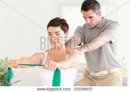 Hübsch Patient einige Übungen unter Aufsicht in einem Raum