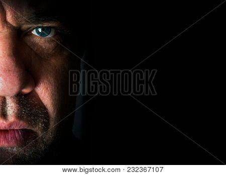 Dark close-up portrait. Sad man half face.
