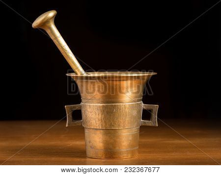 Mortar Made Of Brass Standing On A Brown Wooden Table