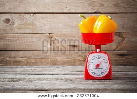 The Yellow Pepper On Red Kitchen Scales