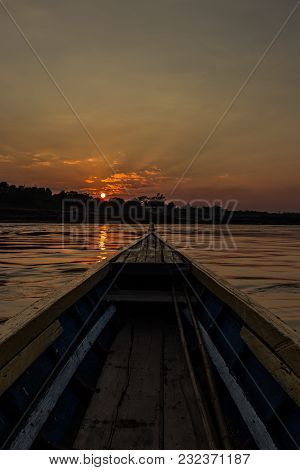 Front view of Old fishing boat with golden sunset as a background