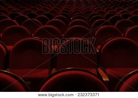 numbered theater chairs with red velvet