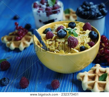 Healthy breakfast with corn flakes, berries, waffle and milk on