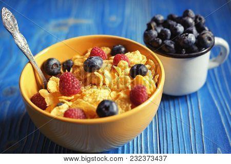 Cornflakes with berries raspberries and blueberries  on blue woo