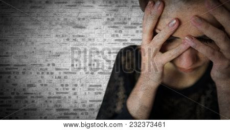 Digital composite of Woman hands over face against white brick wall with grunge overlay