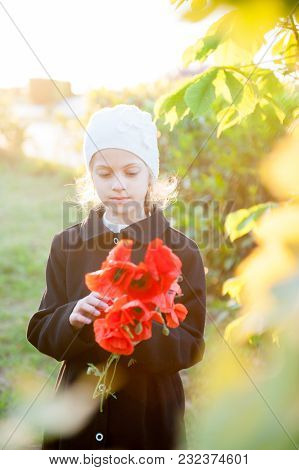 Beautiful Little Girl In Woolen Hat And Coat Holding Bouquet Of Red Flowers In Spring