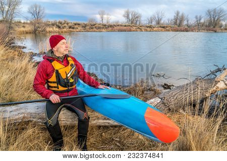 senior male paddler is resting on a lake shore after workout on his racing stand up paddleboard, early spring Colorado scenery