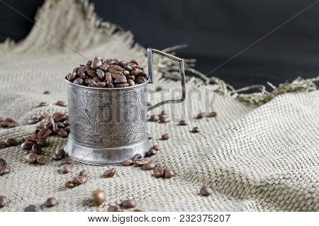 Grains Of Coffee And An Antique Silver Cup Holder On The Table. Still Life, Background