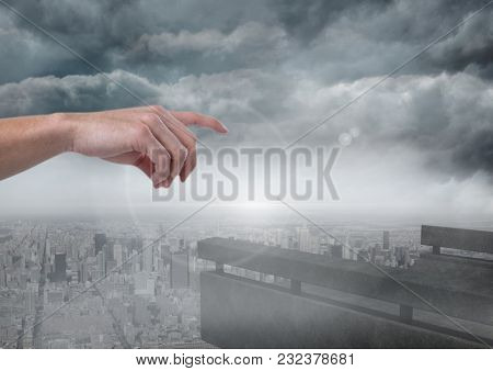 Digital composite of Hand pointing in cloudy sky over city
