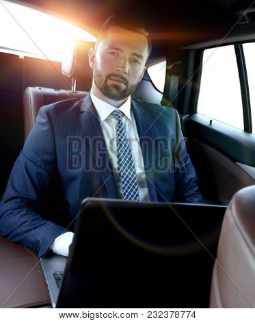 businessman with laptop sitting in a comfortable car