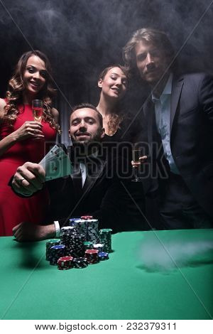 portrait of group of people with drinks playing poker in casino