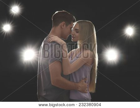 Young loving couple on dark background with backlit