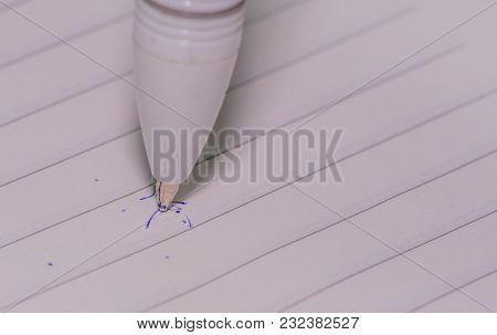 Closeup Of Pen Tip With Standing Vertically On Lined White Paper