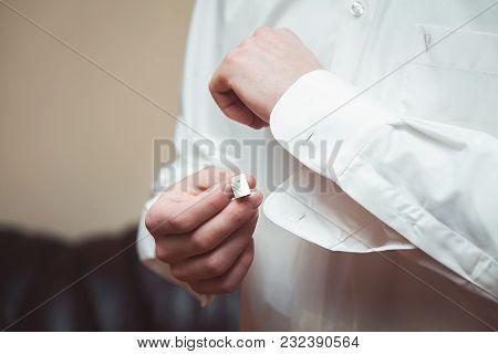 A Man Fastens A White Ceremonial Shirt Close-up.