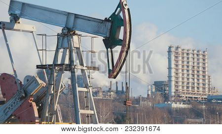 Close-up Of A Working Pump For The Extraction Of Crude Oil And Of A Petrochemical Plant's Pipes Emis