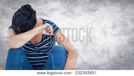 Digital composite of Woman sitting and crying into arm against white wall with grunge overlay