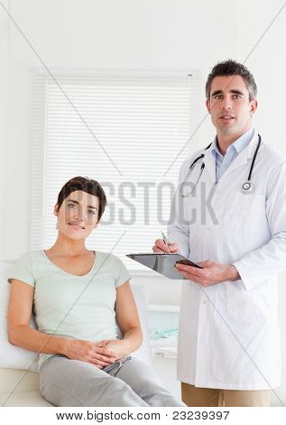 Male Doctor and female patient looking into a camera in a room